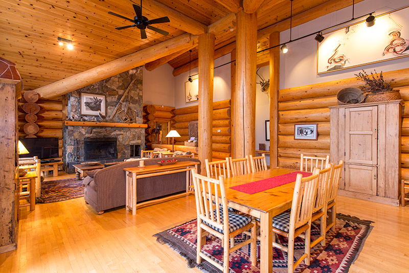Vaulted ceilings in log home living room with massive slate rock fireplace and 18' cedar logs